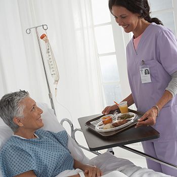 nurse serving patient meal on foam plates